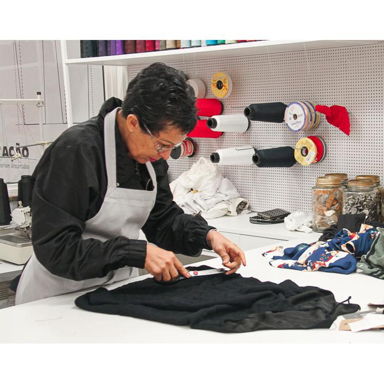 mulher cortando roupa em fabrica
