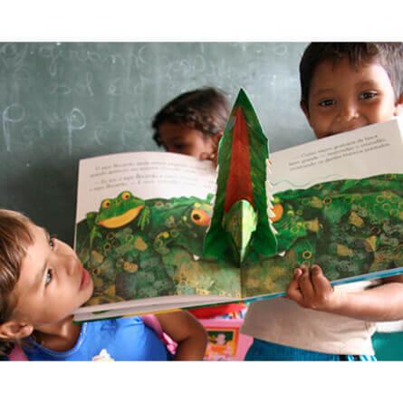 criancas segurando livro sorrindo